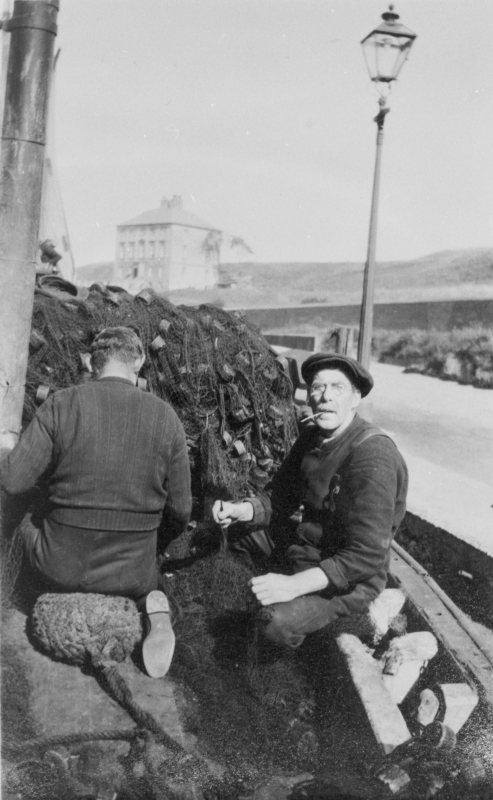 William Dougal, Skipper of 'Amaranth', BK81, at Eyemouth harbour, 1930. The man with his back to the camera is David Lough. In the background, gunscreen house. Original - M. Fairnie via C.Carruthers.