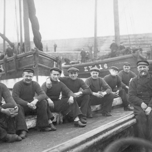 Crew of 'Guide Me', KY301. Taken in Port Dover, Canada, 1906. 'Jessie Hughes', KY416, can be seen in the background. L-R: William Davidson (known in Port Dover as Scotty Bill), Robert Davidson, John Wood, Richard Davidson, Alex Brown, Robert Muir, Alex Muir, Alex Watson, and Captain Robert Davidson