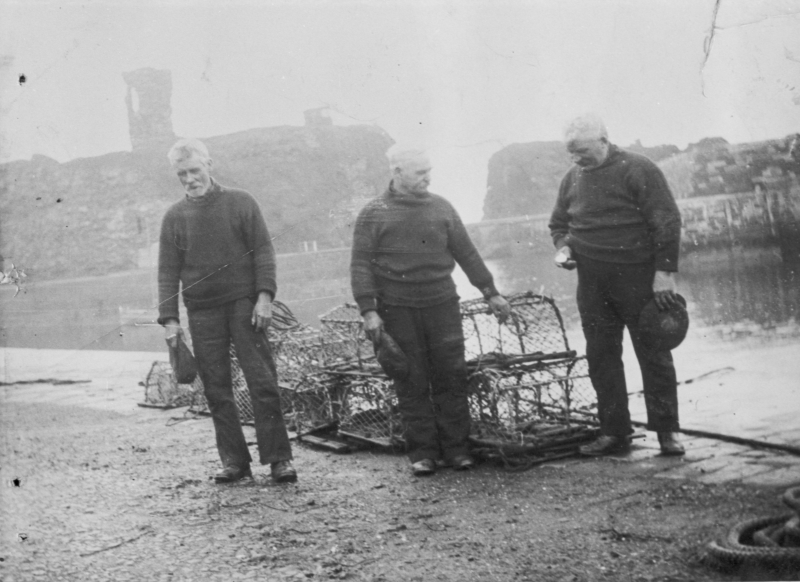 Three fisherman taking part in a two minute silence on Armistice Day, Victoria harbour, Dunbar. L-R: Unknown, unknown, John 'Gallagher' Johnstone. Johnstone was the Skipper of then 3.15 ton 'Isa', LH202. Alex Johnston was the owner. Original - C. Carruthers.