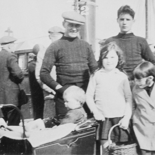 Group of people on Anstruther pier, 1932. Back row, L-R: Phemie Corstorphine, David Corstorphine, David Corstorphine, John Ballingall, Front row, L-R; Sonny Corstorphine (in pram), Unknown Ballingall, Jessie Corstorphine.