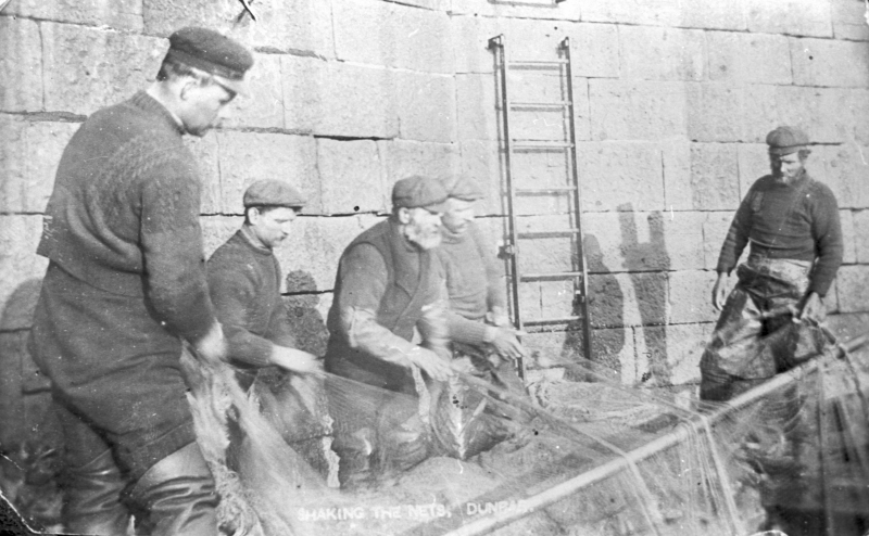 Postcard entitled 'Shaking the nets, Dunbar'. Fishing crew are clearing the nets. L-R: Andrew Robertson, John 'Gee Gee' Smith, Davie Thomson, and 'Tam Pat' Johnston, and Tommy Herkess. A. Robertson was the grandfather of Postmaster's Wife and Davie Thomson later emigrated to Canada.