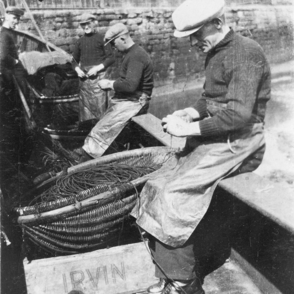 Baiting lines onboard 'Fifeness'. L-R: A. Tawse, P. Doig, A. Watson, and A. Smith. Her Skipper was W. Sutherland. Irvin's were fish buyers based near Edinburgh. Original image from Mrs Johnson Smith.
